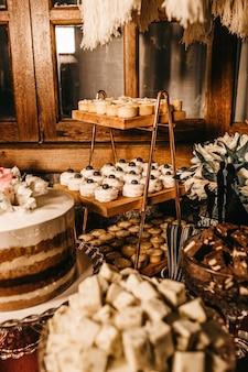Disparo vertical de una mesa de postres con varios deliciosos pasteles bajo la luz