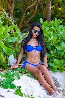 Disparo vertical de un modelo femenino asiático en bikini azul en la playa mirando hacia abajo con modestia