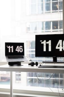 Disparo vertical de un moderno escritorio de oficina con monitores que muestran la hora y auriculares