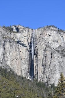 Disparo vertical de montañas con una cascada bajo un cielo azul claro