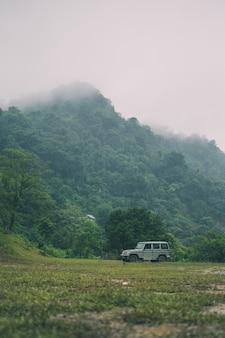Disparo vertical de montañas cubiertas de vegetación y un coche