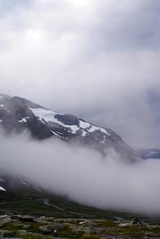 Disparo vertical de montañas rocosas cubiertas de nieve y niebla en noruega