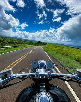 Disparo vertical de una moto en la carretera con la hermosa vista de las montañas en kauai, hawaii