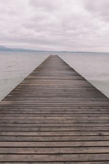 Disparo vertical de un muelle de madera sobre el océano tranquilo bajo el hermoso cielo nublado