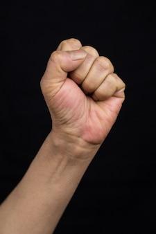 Disparo vertical de una mujer asiática sosteniendo su puño como un signo del concepto de empoderamiento de la fuerza-mujeres