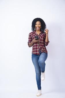 Disparo vertical de una mujer bonita que se siente emocionada mientras usa su teléfono