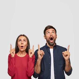 Disparo vertical de una mujer caucásica sorprendida y un hombre apuntando con ambos dedos índices hacia arriba, muestra el espacio libre para la promoción