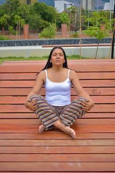 Disparo vertical de una mujer latina meditando en un banco de madera en el parque