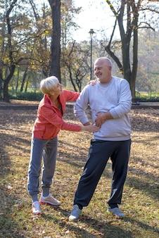 Disparo vertical de una mujer mayor de raza caucásica ayudando a su marido mientras trota en un parque juntos