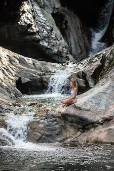 Disparo vertical de una mujer meditando cerca de una cascada