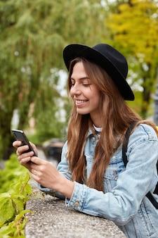 Disparo vertical de mujer de moda alegre lee un mensaje divertido, utiliza la aplicación de teléfono, posa sobre árboles verdes al aire libre