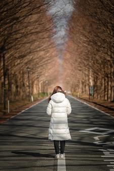 Disparo vertical de una mujer de pie en una carretera vacía