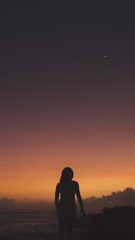 Disparo vertical de una mujer en silueta de pie sobre un acantilado cerca del mar durante la puesta de sol