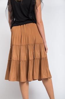 Disparo vertical de una mujer vistiendo una camisa negra y una falda larga de color beige sobre un fondo blanco.
