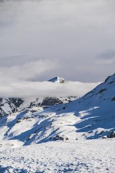 Disparo vertical de niebla en las montañas cubiertas de nieve