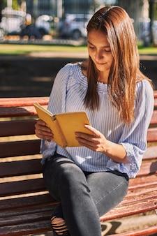 Disparo vertical de una niña con una camisa azul leyendo un libro en el banco