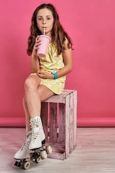 Disparo vertical de una niña en patines sentada en un taburete y bebiendo un jugo