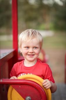 Disparo vertical de un niño caucásico blanco con cabello rubio sosteniendo el volante