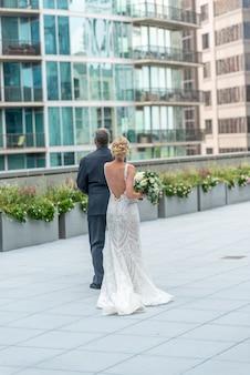 Disparo vertical de una novia y un novio en el hermoso balcón mirando los edificios