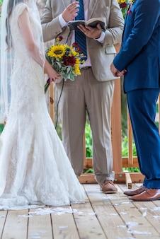 Disparo vertical de la novia y el novio de pie uno frente al otro durante la ceremonia de la boda