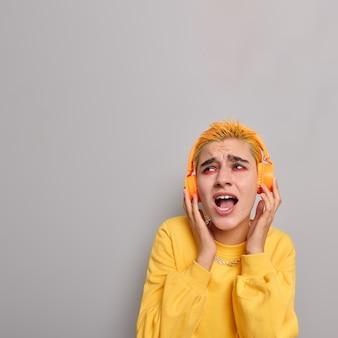 Disparo vertical de optimista chica de pelo amarillo con apariencia inusual maquillaje brillante escucha música en auriculares inalámbricos canta canciones a lo largo aislado sobre pared gris