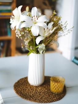 Disparo vertical de orquídeas blancas en un jarrón sobre una mesa dentro de una habitación en madeira, portugal