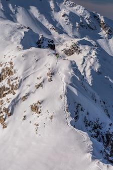 Disparo vertical de un paisaje montañoso cubierto de nieve blanca hermosa en sainte foy, alpes franceses