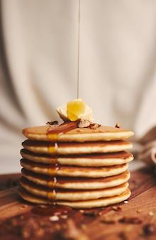 Disparo vertical de panqueques con almíbar, mantequilla y nueces tostadas en una placa de madera