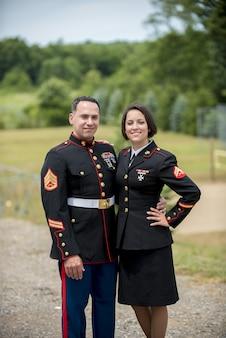 Disparo vertical de una pareja militar abrazándose mientras sonríe a la cámara