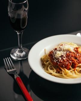 Disparo vertical de pasta con salsa en un recipiente sobre la mesa con una copa de vino tinto