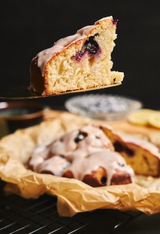 Disparo vertical de un pastel de cerezas con crema e ingredientes en el lado negro
