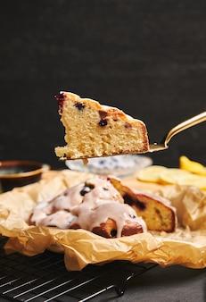 Disparo vertical de un pastel de cerezas con crema e ingredientes en el lateral sobre un fondo negro