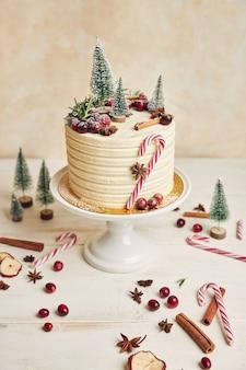 Disparo vertical de un pastel de navidad con bayas y canela y adornos navideños