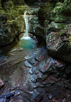 Disparo vertical de una pequeña cascada en la cueva rocosa en el municipio de skrad en croacia