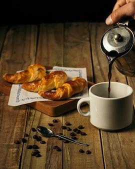 Disparo vertical de una persona vertiendo café en una taza blanca con tres croissants sobre una tabla de madera