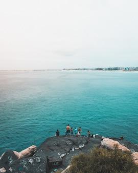 Disparo vertical de pescadores que pescan en el mar azul en río de janeiro.