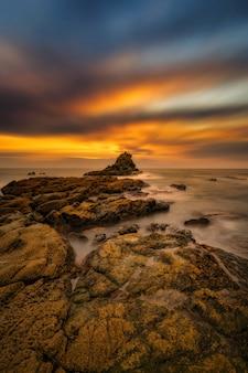 Disparo vertical de las piedras a la orilla del mar bajo el fantástico amanecer