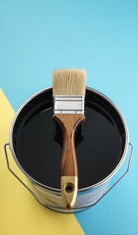 Disparo vertical de pincel de madera en la parte superior de la lata de pintura de color negro con espacio de copia