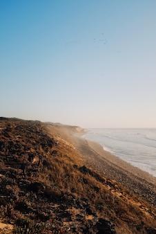 Disparo vertical de playa al amanecer por el mar en calma