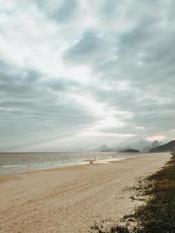 Disparo vertical de una playa rodeada por el mar bajo un cielo nublado en río de janeiro, brasil