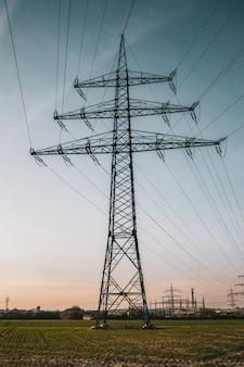 Disparo vertical de un poste eléctrico bajo un cielo nublado azul