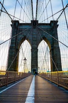Disparo vertical de un puente de brooklyn en la ciudad de nueva york con una hermosa puesta de sol