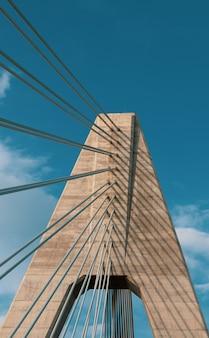 Disparo vertical de un puente bajo un cielo azul nublado