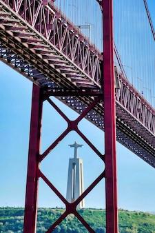 Disparo vertical de un puente con la estatua de cristo en lisboa, portugal.