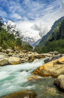 Disparo vertical de un rápido río chocando contra las rocas con montañas