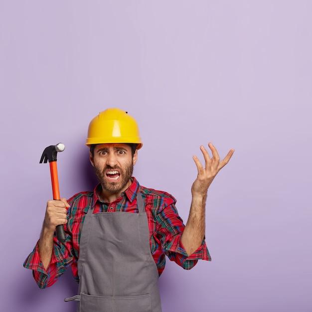 Disparo vertical de reparador frustrado tiene expresión de cara perpleja, martillo en mano, levanta el brazo con indignación, vestido con ropa de trabajo, no puede entender qué reparar