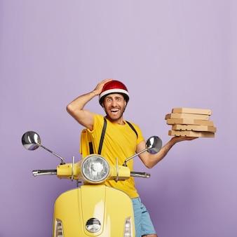 Disparo vertical de repartidor asustado conduciendo scooter amarillo mientras sostiene cajas de pizza
