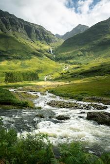 Disparo vertical de un río rodeado por montañas y prados en escocia