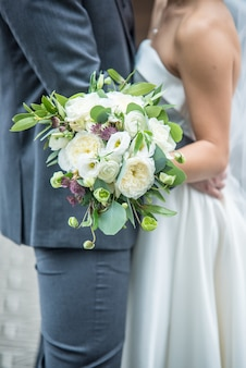 Disparo vertical de un romántico novio y novia sosteniendo un ramo de novia
