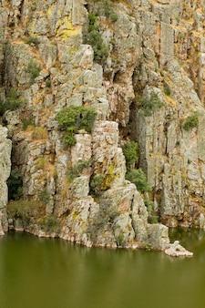 Disparo vertical del salto del gitano en el parque nacional de monfragüe en españa, con un lago verde